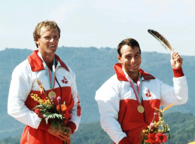 Alwyn Morris avec la plume et la médaille d'or et son coéquipier Hugh Fisher sur le podium du K-2 1000 m des Jeux de Los Angeles 1984.